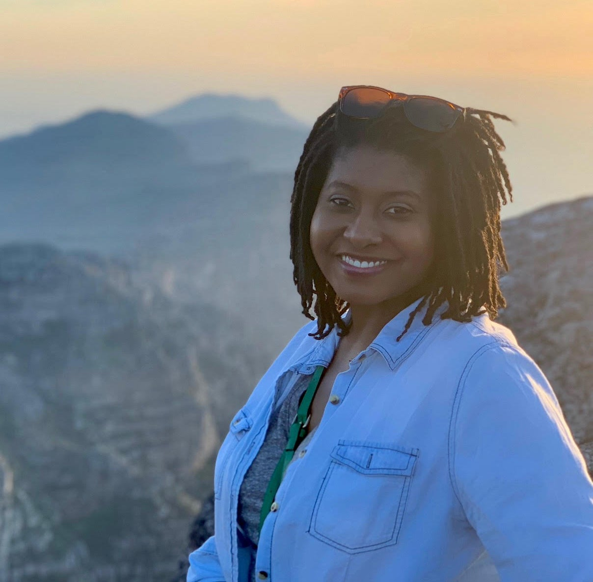 """""""Denisha Jenkins smiles at the camera while the sun sets in the background over mountains."""""""