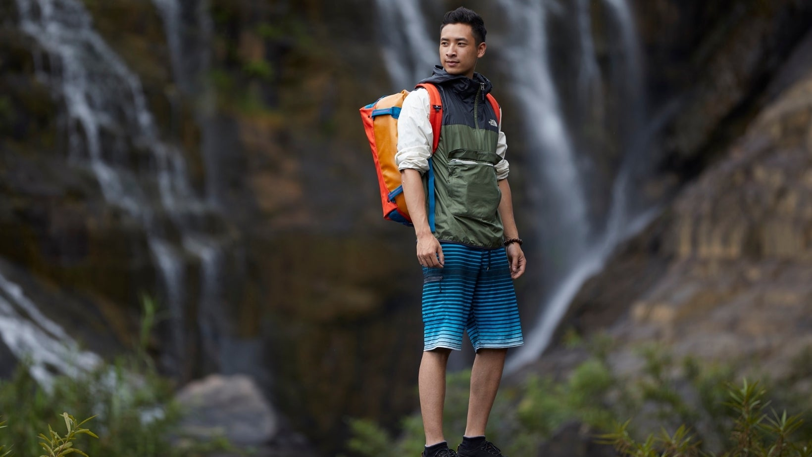 Man with Eagle Creek backpack standing in front of a waterfall